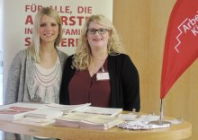 Unsere Ansprechpartnerin Julia mit unserer Studentin Ines auf dem Themenabend Promotion. Sie stehen am Infostand und schauen in die Kamera. (Foto: ArbeiterKind.de)