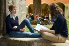 Landesschule Pforta: Schülerinnen lernen draußen, eine hält einen Apfel in der Hand. Im Hintergrund ein großer Baum um den auf einer Bank mehrere Schülerinnen und Schüler sitzen. (Foto: Landesschule Pforta/ Photo-Tempel)