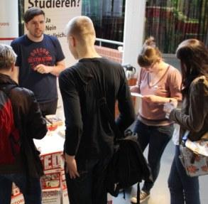 Info-Stand von ArbeiterKind.de beim Tag des Stipendiums: Student spricht zu mehreren Besuchern (Foto: ArbeiterKind.de/Wolf Dermann)