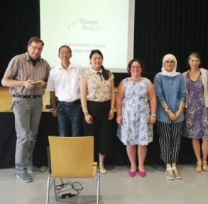 Gruppenfoto von unserem Schulvortrag an der Käthe-Kollwitz-Schule. Im Hintergrund läuft unsere Präsenation und vor der Bühne lächeln alle in die Kamera. (Foto: ArbeiterKind.de)